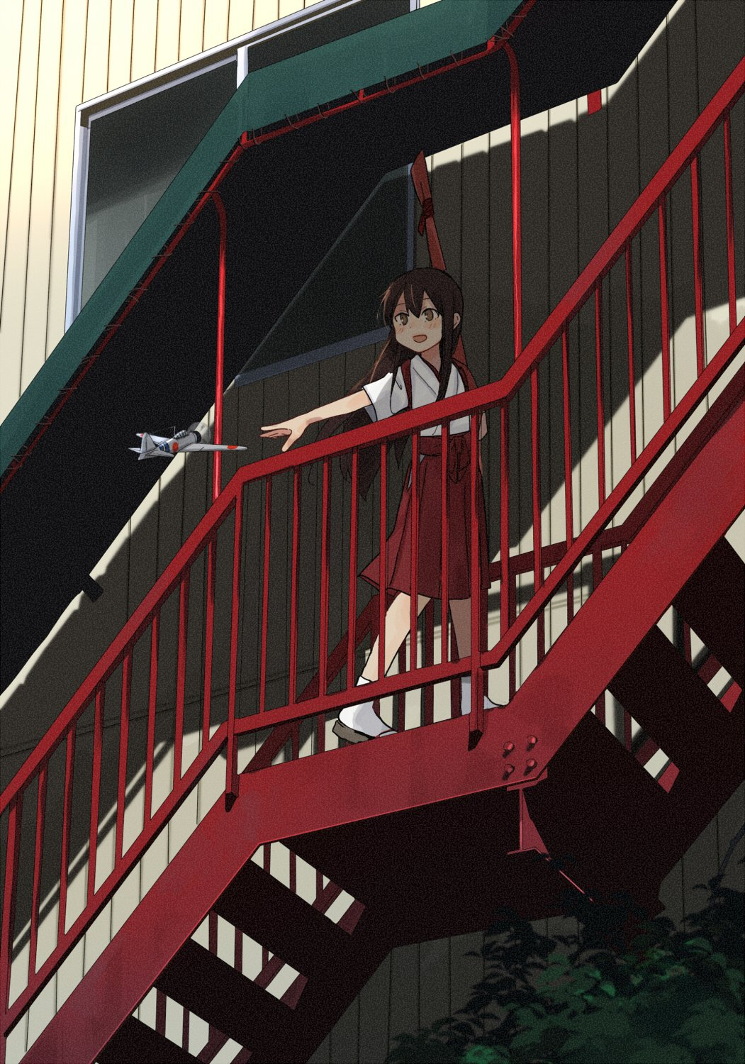 1girl a6m_zero aircraft airplane akagi_(kantai_collection) annin_musou brown_eyes brown_hair geta hakama_skirt highres japanese_clothes kantai_collection long_hair open_mouth red_skirt skirt smile solo stairs straight_hair tabi younger