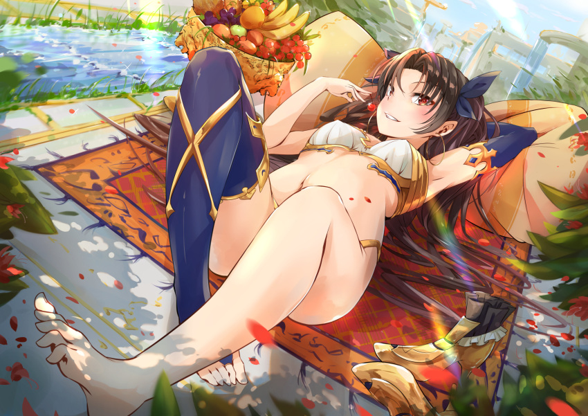 1girl arm_behind_head banana barefoot black_hair blue_gloves blue_legwear blush breasts cherry earrings elbow_gloves faicha fate/grand_order fate_(series) feet food fruit gloves grapes hair_ribbon highres hoop_earrings ishtar_(fate/grand_order) jewelry long_hair looking_at_viewer lying midriff navel on_back pillow red_eyes ribbon shoes_removed single_elbow_glove single_thighhigh small_breasts solo thigh-highs toes towel two_side_up