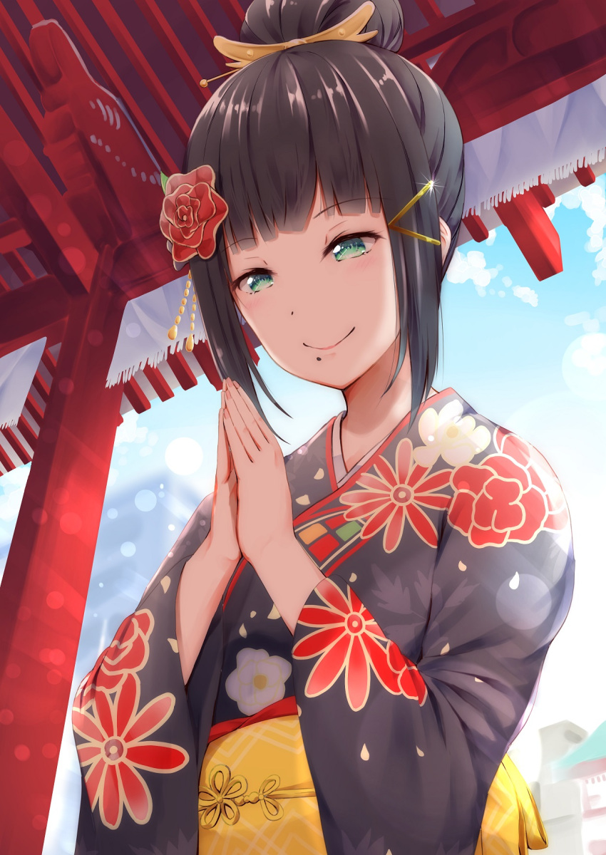 1girl alternate_hairstyle bangs black_kimono blue_sky blunt_bangs clouds eyebrows_visible_through_hair floral_print flower green_eyes hair_bun hair_flower hair_ornament hairpin hands_together hatsumoude hayaoki_(asagi-iro_seishun-bu) highres japanese_clothes kimono kurosawa_dia light_blush light_particles long_sleeves love_live! love_live!_sunshine!! mole mole_under_mouth new_year outdoors praying red_flower sash sidelocks sky smile solo temple traditional_clothes upper_body wide_sleeves x_hair_ornament yellow_sash