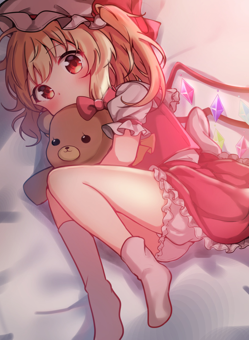 1girl absurdres ascot ass back_bow bangs blonde_hair bloomers blush bow covering_mouth crystal eyebrows_visible_through_hair feet flandre_scarlet foot_out_of_frame hanen_(borry) hat hat_ribbon highres holding holding_stuffed_toy hug knees_to_chest looking_at_viewer lying mob_cap on_side petticoat puffy_short_sleeves puffy_sleeves red_bow red_eyes red_ribbon red_skirt red_vest ribbon shirt short_hair short_sleeves skirt skirt_set socks solo stuffed_animal stuffed_toy teddy_bear touhou underwear vest white_bow white_headwear white_legwear white_shirt wings yellow_neckwear