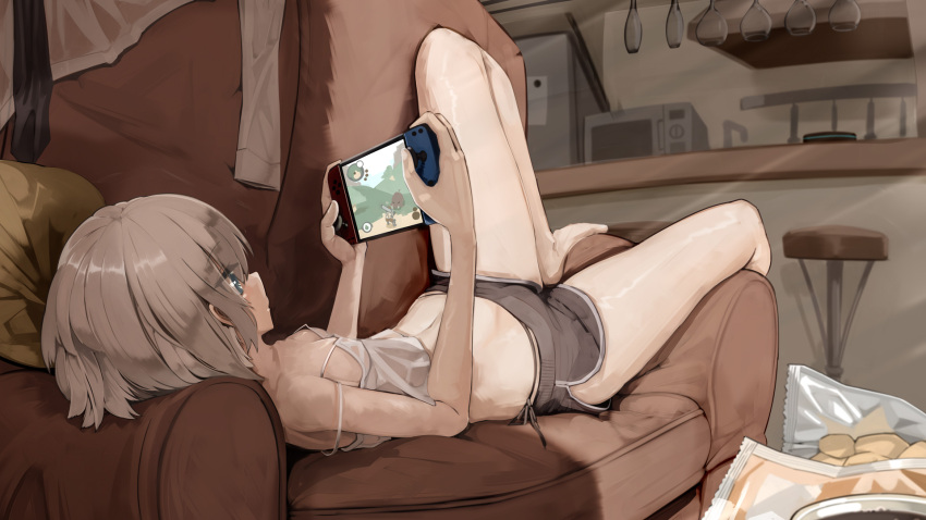 1girl barefoot blue_eyes breasts brown_hair commentary_request couch genek grey_shorts handheld_game_console highres holding holding_handheld_game_console indoors legs lying navel nintendo_switch on_back on_couch original short_hair short_shorts shorts small_breasts solo thighs
