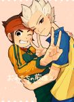2boys blush brown_hair endou_mamoru goalkeeper gouenji_shuuya grin headband hug inazuma_eleven inazuma_eleven_(series) looking_at_viewer male multiple_boys one_eye_closed raimon raimon_soccer_uniform short_hair smile v yaoi