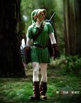 1boy belt blonde_hair boot cosplay forest full_body link male photo pointy_ears shield sword the_legend_of_zelda tunic wings