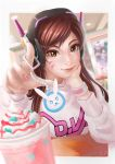 +_+ 1girl bangs beads blurry brown_eyes brown_hair casual charm_(object) chin_rest clothes_writing cup d.va_(overwatch) depth_of_field dessert drink emblem eyelashes facial_mark food headphones index_finger_raised indoors lips long_hair long_sleeves looking_at_viewer mecha meka_(overwatch) nail_art nail_polish nose overwatch pink_nails reaching restaurant signature smile solo subaru01rins sweatshirt swept_bangs tsurime upper_body whipped_cream whisker_markings wristband
