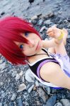 blue_eyes cosplay jewelry kairi kingdom_hearts lowres necklace photo red_hair redhead short_hair sitting solo