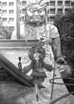 1girl bag beads building city greyscale japanese_clothes katou_fumitaka looking_at_viewer looking_up monk monochrome original prayer_beads rooftop rope solo staff standing standing_on_one_leg statue tabi tree