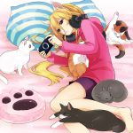 1girl animal_ears bed black_cat black_shorts blonde_hair brown_eyes calico casual cat cat_ears cat_paw closed_mouth fake_animal_ears girls_und_panzer grey_cat hair_between_eyes handheld_game_console headphones headphones_around_neck hood hoodie kosame_koori long_hair long_sleeves lying nekonyaa on_side paw_print playstation_vita purple_shirt shirt shorts solo striped_pillow white_cat