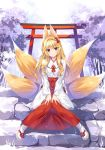 1girl animal_ears bangs blonde_hair blush breasts brown_eyes fox_ears fox_tail full_body hair_intakes hair_ornament hakama japanese_clothes knees_together_feet_apart long_hair long_sleeves looking_at_viewer miko multiple_tails original oryou outdoors sandals sitting sitting_on_stairs smile snowing solo stairs tabi tail torii tree v_arms white_legwear wide_sleeves