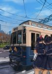 2girls black_hair blurry bow cable car city cowboy_shot depth_of_field finanl ground_vehicle hair_bow highres motor_vehicle multiple_girls original outdoors ponytail power_lines road school_uniform sky street streetcar train tree