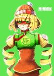 1girl :/ al_bhed_eyes arms_(game) bangs beanie blonde_hair blunt_bangs breasts character_name closed_mouth clothes_writing cowboy_shot crop_top facing_viewer food green_background green_eyes green_shirt hat highres knit_hat lips looking_away looking_to_the_side madarame min_min_(arms) noodles orange_hat outline pink_lips shirt short_eyebrows short_hair simple_background small_breasts solo standing thick_eyebrows tsurime turtleneck uneven_eyes white_outline zipper zipper_pull_tab