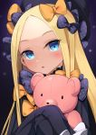 1girl :o abigail_williams_(fate/grand_order) bangs black_background black_bow black_dress black_hat blonde_hair blue_eyes blush bow commentary_request dress fate/grand_order fate_(series) hair_bow hands_in_sleeves hat head_tilt lo_xueming long_sleeves looking_at_viewer object_hug orange_bow parted_bangs parted_lips polka_dot polka_dot_bow simple_background solo stuffed_animal stuffed_toy teddy_bear