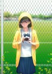 1girl absurdres black_eyes black_hair blurry bow bowtie camera chain-link_fence cowboy_shot depth_of_field fence highres hood hoodie mole mole_under_eye original rungsak_sontayanont school_uniform short_hair skirt solo