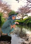 1girl bangs bent_knee blue_eyes blue_footwear blue_hair blue_shirt blue_skirt blurry blurry_background boots branch breasts bush cherry_blossoms commentary_request concrete eyebrows_visible_through_hair eyelashes fishing fishing_rod flanvia flat_cap full_body grass green_hat hair_bobbles hair_ornament hand_on_thighs hat heel_raised highres holding_branch kawashiro_nitori large_breasts long_sleeves looking_at_viewer o3o one_side_up outdoors petals petals_on_water photo_background pipeline pocket river shirt skirt solo squatting touhou tree