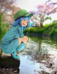1girl bangs bent_knee blue_eyes blue_footwear blue_hair blue_shirt blue_skirt blurry blurry_background boots branch breasts bush cherry_blossoms commentary_request concrete d: eyebrows_visible_through_hair eyelashes fishing fishing_rod flanvia flat_cap full_body grass green_hat hair_bobbles hair_ornament hand_on_thighs hat heel_raised highres holding_branch kawashiro_nitori large_breasts long_sleeves looking_at_viewer one_side_up open_mouth outdoors petals petals_on_water photo_background pipeline pocket pulling river shirt skirt solo squatting tongue touhou tree upper_teeth