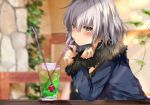 1girl bangs bendy_straw blue_jacket blurry blurry_background blush brown_eyes closed_mouth commentary_request cup depth_of_field drink drinking_glass drinking_straw eyebrows_visible_through_hair fate/grand_order fate_(series) fur-trimmed_jacket fur-trimmed_sleeves fur_trim hair_between_eyes hand_up indoors jacket jeanne_d'arc_(alter)_(fate) jeanne_d'arc_(fate)_(all) long_sleeves looking_at_viewer pon_(ponidrop) silver_hair sleeves_past_wrists solo wicked_dragon_witch_ver._shinjuku_1999