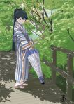 1girl black_eyes black_hair bridge closed_umbrella dappled_sunlight full_body houshou_(kantai_collection) japanese_clothes kantai_collection kimono looking_down mihama_machi ponytail sandals solo standing striped striped_kimono sunlight tree umbrella yukata