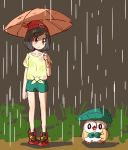 1girl beanie black_hair closed_mouth creatures_(company) game_freak gen_7_pokemon green_shorts hat holding holding_umbrella leaf_umbrella meka_(77111994) mizuki_(pokemon) nintendo orange_umbrella pokemon pokemon_(creature) pokemon_(game) pokemon_sm rain red_hat rowlet shirt short_hair short_sleeves shorts standing tied_shirt umbrella