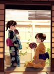 2girls black_eyes black_kimono brown_hair commentary_request fan fence fingernails floral_print flower from_behind hair_flower hair_ornament holding ivy japanese_clothes kimono looking_at_viewer looking_back multiple_girls munakata_(hisahige) orange_flower orange_kimono original paper_fan parted_lips plant ponytail porch potted_plant short_hair sitting uchiwa wooden_fence yukata