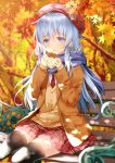 1girl alternate_costume beret black_legwear blue_eyes blush brown_coat brown_sweater buttons coat eyebrows_visible_through_hair food hair_between_eyes hat hibiki_(kantai_collection) highres holding holding_food kantai_collection leaf long_hair maple_leaf maple_tree motohara_moka necktie open_mouth pleated_skirt purple_scarf red_hat red_neckwear red_skirt scarf silver_hair sitting skirt solo sweater thigh-highs tree