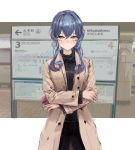 1girl alternate_costume black_pants black_sweater blue_eyes blue_hair brown_coat coat commentary_request cowboy_shot crossed_arms gotland_(kantai_collection) hair_bun highres kantai_collection long_hair looking_at_viewer mole mole_under_eye pants photo_background sign solo standing sweater tifg39