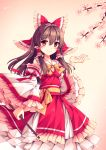 1girl adapted_costume blush bow breasts brown_hair cleavage floating_hair flower frilled_bow frilled_hair_tubes frilled_sleeves frills hair_between_eyes hair_bow hair_tubes hakurei_reimu highres holding layered_skirt long_hair long_skirt long_sleeves looking_at_viewer mechrailgun pink_background pink_flower red_bow red_eyes red_ribbon red_shirt red_skirt ribbon shiny shiny_hair shirt skirt sleeveless sleeveless_shirt small_breasts smile solo standing touhou white_sleeves wide_sleeves yellow_neckwear