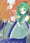 1girl autumn autumn_leaves bare_shoulders blue_skirt blue_sky closed_mouth collared_shirt commentary_request detached_sleeves dutch_angle eyebrows_visible_through_hair frog_hair_ornament green_eyes green_hair hair_ornament hair_tubes highres holding holding_leaf holding_stick kochiya_sanae leaf long_hair long_skirt looking_at_viewer shelk787 shiny shiny_hair shirt skirt sky sleeveless sleeveless_shirt sleeves_past_wrists smile snake_hair_ornament solo stick torii touhou white_shirt