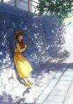 1girl bangs blue_feathers braid brown_eyes brown_hair camera commentary_request dappled_sunlight day dress feathers hat holding holding_camera long_hair looking_away nemoto_yuuma open_mouth original outdoors sandals sleeveless sleeveless_dress solo standing sun_hat sunlight twin_braids twintails yellow_dress