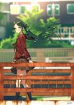 1girl artist_name black_legwear blew_andwhite blurry blurry_background blush brown_serafuku building day green_eyes green_hair hair_ribbon highres kantai_collection kneehighs long_hair long_neck long_sleeves looking_at_viewer mikuma_(kantai_collection) outdoors railing red_ribbon ribbon school_uniform skirt smile solo standing twintails very_long_hair