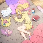 1girl alternate_costume bed blonde_hair book closed_mouth computer green_eyes headphones hood hood_down laptop lillie_(pokemon) long_hair long_sleeves lying mifa nintendo_switch on_side open_book pillow pokemon pokemon_(game) pokemon_sm ponytail shorts slippers solo