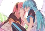 2girls :t blue_eyes blue_hair commentary eye_contact hand_on_another's_chin hatsune_miku head_to_head headband heart leaning_forward long_hair looking_at_another megurine_luka multiple_girls nail_polish pants pillow pink_hair short_sleeves sitting straight_hair track_pants twintails twitter_username very_long_hair vocaloid wanaxtuco yuri