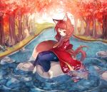 1girl animal_ear_fluff animal_ears autumn bandaged_feet bangs blue_hakama braid brown_hair commentary english_commentary finger_to_mouth floral_print fox_ears fox_girl fox_tail fuyusuke_(hz+) hair_ornament hairclip hakama hand_up highres japanese_clothes kimono long_hair long_sleeves looking_at_viewer original parted_lips print_kimono red_eyes red_kimono sitting solo tail tree very_long_hair water wide_sleeves