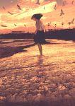 1girl animal beach bird black_skirt brown_hair evening floating_hair flock from_side gemi highres lamppost medium_hair ocean orange_sky original scenery seagull sepia shore skirt skirt_hold sky solo standing wading