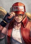 1boy baseball_cap black_gloves blonde_hair blue_eyes clothes_writing collarbone commentary_request copyright_name fatal_fury fingerless_gloves floating_hair gloves hair_between_eyes hand_on_headwear hat highres kuroi_susumu long_hair looking_at_viewer male_focus muscle open_clothes open_vest parted_lips ponytail red_headwear red_vest shadow smile snk solo super_robot_wars terry_bogard the_king_of_fighters unzipped upper_body vest white_tank_top