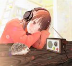 1girl blurry blurry_background blush brown_eyes brown_hair cable commentary_request head_on_arm headphones hedgehog listening nakamura_hinata original radio radio_antenna red_sweater short_hair solo sweater table