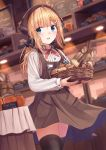 1girl absurdres ahoge apron bakery bangs basket black_legwear black_ribbon blonde_hair blue_eyes blue_skirt blurry blurry_background blurry_foreground blush bread brown_apron commentary_request copyright_request depth_of_field eyebrows_visible_through_hair food hair_ornament hair_ribbon hairclip head_scarf highres holding holding_basket indoors long_hair long_sleeves looking_at_viewer low_ponytail n2_(yf33) name_tag open_mouth orange_juice pen red_neckwear ribbon round_teeth shirt shop skirt solo teeth thigh-highs uniform upper_teeth white_shirt