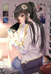 1girl absurdres ahoge barefoot black_hair blue_shorts blurry blurry_background book brown_eyes depth_of_field flower from_behind hair_flower hair_ornament hairclip highres holding jacket knees_up long_hair long_sleeves looking_at_viewer looking_back nintendo_switch original picture_frame ponytail rosuuri scan short_shorts shorts sidelocks sitting solo thighs white_jacket