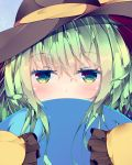 1girl black_headwear blue_background commentary_request covering_mouth eyebrows_visible_through_hair fant frilled_sleeves frills green_eyes green_hair hair_between_eyes hat hat_ribbon highres komeiji_koishi light_blush long_sleeves looking_at_viewer partial_commentary ribbon shirt short_hair simple_background sleeves_past_fingers sleeves_past_wrists solo third_eye touhou upper_body yellow_shirt