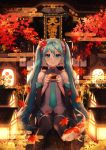 1girl absurdres air_bubble aqua_eyes aqua_hair aqua_neckwear autumn_leaves bangs black_legwear bubble camellia collared_shirt commentary_request detached_sleeves ema fish flower flying_fish goldfish grey_shirt hair_flower hair_ornament hatsune_miku highres holding holding_ema huge_filesize koi lantern long_hair looking_at_viewer miniskirt necktie peta_(snc7) pink_flower red_flower ribbon-trimmed_sleeves ribbon_trim shirt sidelocks sitting skirt smile solo thigh-highs very_long_hair vocaloid