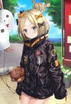 1girl abigail_williams_(fate/grand_order) bandaid_on_forehead bangs black_bow black_jacket blonde_hair blue_eyes blush bow closed_mouth commentary_request crossed_bandaids fate/grand_order fate_(series) forehead hair_bow hair_bun harimoji heroic_spirit_traveling_outfit high_collar holding_balloon jacket long_hair long_sleeves looking_at_viewer multiple_bows orange_belt orange_bow park parted_bangs polka_dot polka_dot_bow sleeves_past_fingers sleeves_past_wrists solo stuffed_animal stuffed_toy teddy_bear tree