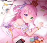 1girl bed blush breasts candy commentary_request controller crown cupcake dress earrings food game_controller heterochromia himemori_luna hololive jewelry long_hair looking_at_viewer lying naomi_(fantasia) nintendo_switch pillow pink_hair solo tray virtual_youtuber