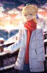 1girl ahoge artoria_pendragon_(all) bangs blonde_hair blue_eyes blue_ribbon braid braided_bun breath clouds coat commentary cowboy_shot elker evening eyebrows_visible_through_hair fate/stay_night fate_(series) green_eyes hair_between_eyes hair_ribbon highres lighthouse long_sleeves looking_at_viewer multicolored multicolored_eyes ocean outdoors railing red_scarf ribbon saber scarf short_hair sidelocks sleeves_past_wrists smile snow snowing standing sunset white_coat winter winter_clothes