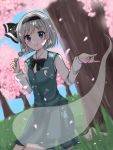 1girl :t arms_up bangs barefoot black_neckwear blue_eyes blue_sky blurry blurry_background blurry_foreground bow bowtie cherry_blossoms commentary_request dango dappled_sunlight day depth_of_field dutch_angle eating eyebrows_visible_through_hair food grass green_skirt green_vest hair_ribbon hanami highres holding_skewer konpaku_youmu konpaku_youmu_(ghost) light_particles long_sleeves looking_at_viewer outdoors petals pleated_skirt ribbon riruku sanshoku_dango seiza shirt short_hair silver_hair sitting skirt skirt_set sky solo sunlight touhou tree under_tree vest wagashi white_shirt