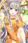 1girl :d bangs blurry blurry_background blush bow braid candy clothes_writing collarbone commentary_request crown_braid depth_of_field eyebrows_visible_through_hair food fujima_takuya grey_eyes grey_hair hair_bow hair_ornament hairclip holding holding_food holding_lollipop hood hood_down hoodie indoors knee_up lollipop long_hair long_sleeves looking_at_viewer one_side_up open_mouth orange_hoodie original plant potted_plant sitting sleeves_past_wrists smile solo star very_long_hair yellow_bow
