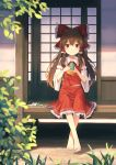 1girl absurdres ascot bangs barefoot blurry_foreground bow brown_hair closed_mouth detached_sleeves eyebrows_visible_through_hair floating_hair frilled_bow frilled_hair_tubes frilled_skirt frills hair_between_eyes hair_bow hair_tubes hakurei_reimu highres long_hair long_sleeves looking_at_viewer medium_skirt orange_neckwear outdoors red_bow red_eyes red_shirt red_skirt ribbon-trimmed_sleeves ribbon_trim shirt sitting skirt sleeveless sleeveless_shirt smile solo touhou very_long_hair white_sleeves yaruwashi