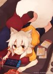 1girl animal_ear_fluff animal_ears bike_shorts blush chips couch fang food fox_ears fox_girl fox_tail lying manga_(object) nintendo_switch off_shoulder on_stomach orange_eyes original pillow rimukoro skin_fang soda_bottle tail white_hair