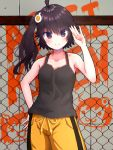 1girl ahoge araragi_karen bakemonogatari black_eyes black_hair blush breasts chain-link_fence closed_mouth collarbone drawstring eniguma. eyebrows_visible_through_hair fence graffiti looking_at_viewer medium_hair monogatari_(series) shorts side_ponytail small_breasts smile tank_top yellow_shorts
