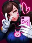 1girl absurdres brown_eyes brown_hair closed_mouth d.va_(overwatch) face facial_mark gloves headphones heart highres holding holding_phone long_hair one_eye_closed overwatch phone pink_background self_shot smile solo upper_body v whisker_markings white_gloves yoons