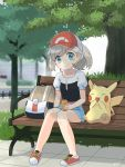 1girl 30re ayumi_(pokemon) backpack backpack_removed bag bangs baseball_cap bench blush can closed_mouth collarbone commentary_request day eyelashes gen_1_pokemon grass hat highres holding holding_can knees_together_feet_apart looking_at_viewer on_bench outdoors pigeon-toed pikachu pokemon pokemon_(creature) pokemon_(game) pokemon_lgpe short_sleeves sitting smile tile_floor tiles tree two-tone_headwear