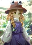 1girl animal_print bangs blonde_hair bloom blurry blurry_background blush brown_headwear closed_mouth commentary_request cowboy_shot frog_print hat highres long_hair long_sleeves moriya_suwako multicolored multicolored_background murasaki_tsutsuji parted_bangs purple_sash purple_skirt purple_vest sash shirt sidelocks skirt skirt_set sleeves_past_wrists standing touhou turtleneck v-shaped_eyebrows vest white_shirt wide_sleeves yellow_eyes