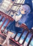 1girl :o backpack bag bangs beret black_footwear blue_dress blue_eyes blue_hair blue_headwear blue_umbrella blurry blurry_foreground blush building chinomaron commentary_request day depth_of_field dress eyebrows_visible_through_hair frilled_legwear from_behind gochuumon_wa_usagi_desu_ka? hair_between_eyes hair_ornament hat highres holding holding_umbrella kafuu_chino long_hair long_sleeves looking_at_viewer looking_back outdoors parted_lips railing rain river shirt shoes sleeveless sleeveless_dress sleeves_past_wrists solo standing thigh-highs two_side_up umbrella very_long_hair walking water water_drop white_legwear white_shirt x_hair_ornament